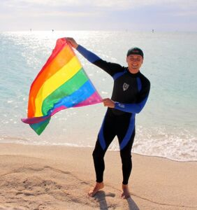 This sexy travel guru lives in a van and is literally planting the rainbow flag everywhere he goes