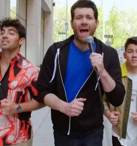 Billy Eichner chases after strangers to inform them the Jonas Brothers are making a comeback