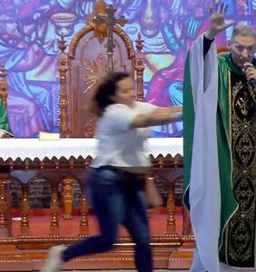 Woman shoves mega-famous anti-gay priest offstage in front of 50,000 praying Catholics